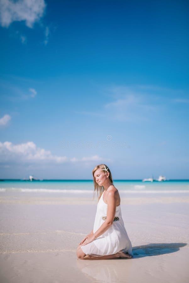 Plenerowy portret młody blondynka modela obsiadanie na plaży z białą rozgwiazdą w włosy zdjęcia royalty free