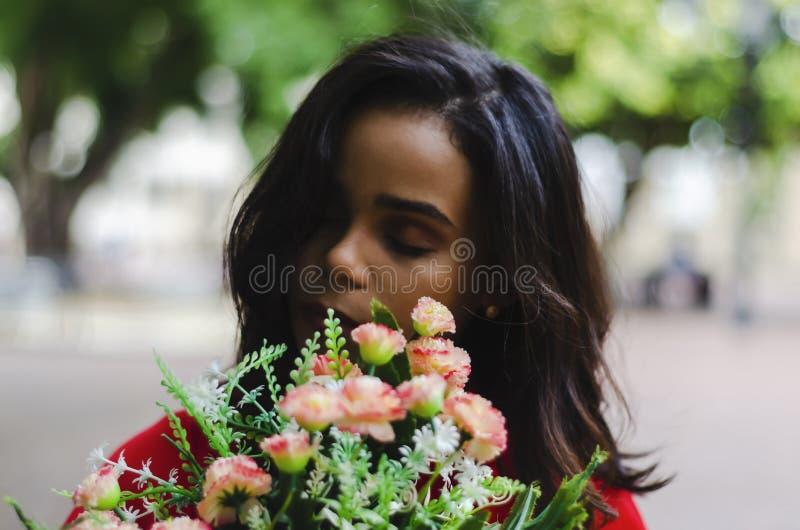 Plenerowy portret młody piękny dziewczyny 19, 25 lat brunetka obwąchiwać bukiet kwiaty Być ubranym czerwonego bluzki miasto fotografia stock