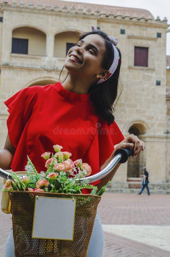 Plenerowy portret młody piękny dziewczyny 19, 25 lat pozuje w ulicie brunetka jechać retro projektującego bicykl nosi? czerwony obrazy stock