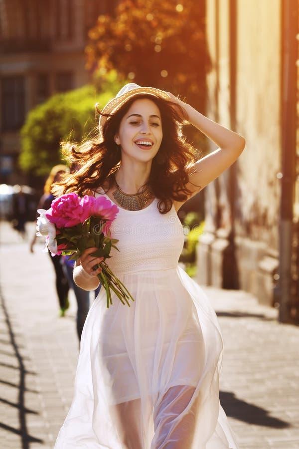Plenerowy portret młody piękny szczęśliwy uśmiechnięty damy odprowadzenie na starej ulicie Wzorcowi jest ubranym eleganccy biel u fotografia stock
