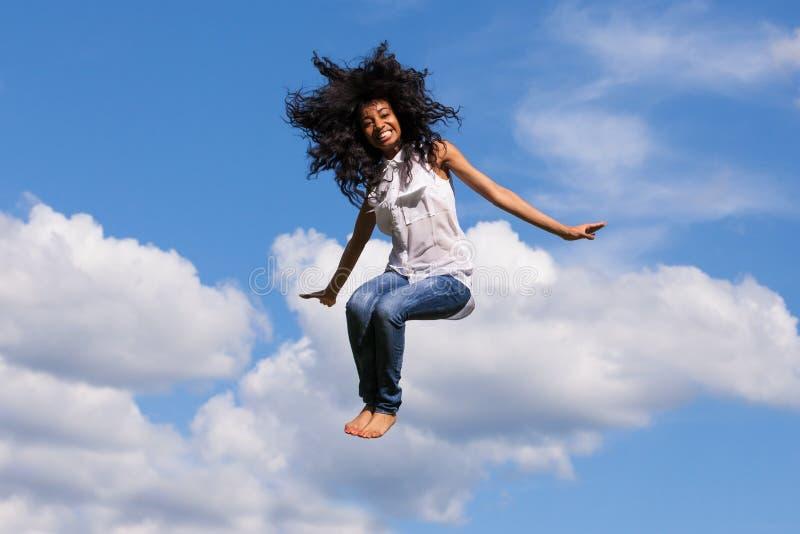 Plenerowy portret nastoletnia czarna dziewczyna skacze nad niebieskim niebem fotografia royalty free
