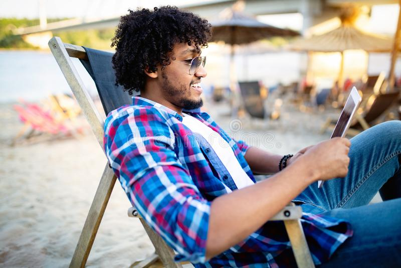 Plenerowy portret szczęśliwy młody afrykański mężczyzna używa pastylka komputer zdjęcia royalty free
