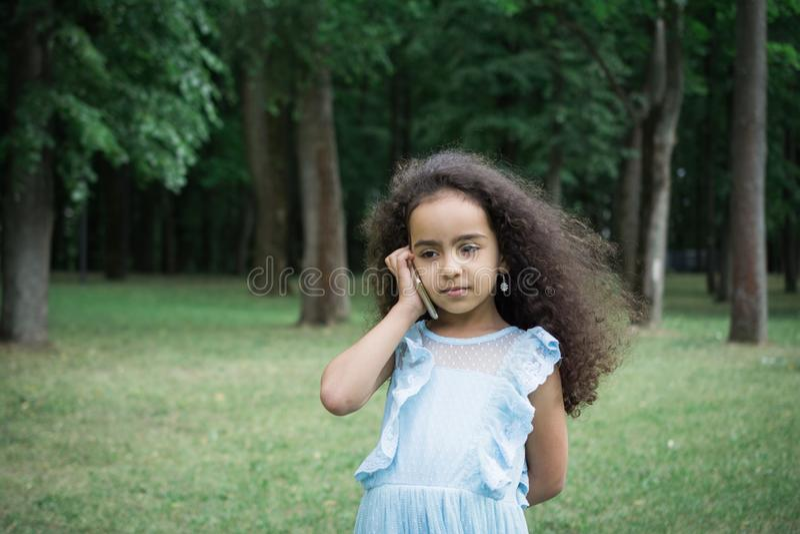 Plenerowy portret szczęśliwy dziewczyny 5-6 roczniak opowiada na telefonie zdjęcia royalty free