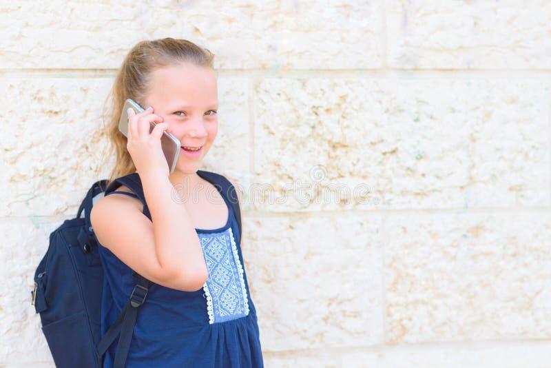 Plenerowy portret szcz??liwy dziewczyny 8-9 roczniak opowiada na telefonie obrazy stock