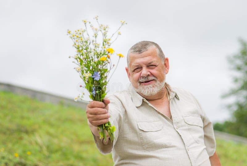 Plenerowy portret uśmiechnięty starszy mężczyzna daje bukietowi zdjęcia stock