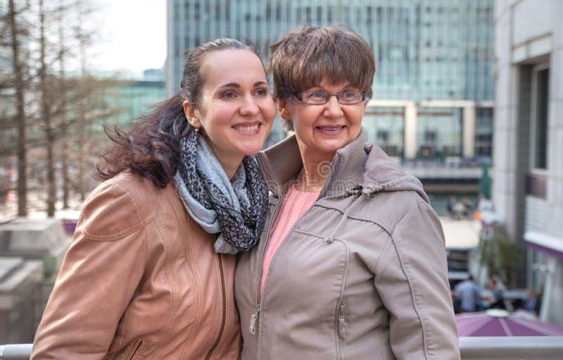 Plenerowy rodzinny portret Macierzysty wiek emerytalny i jej córka w mieście, uśmiechnięty i patrzejący wokoło Dwa pokolenie, szc fotografia royalty free