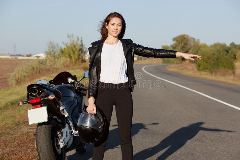 Plenerowy strzał żeński rowerzysta hitchhikes na drodze, trzyma hełm w jeden ręce, jest ubranym skórzaną kurtkę, zatrzymuje inneg zdjęcie royalty free