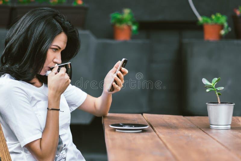 Plenerowy strzał Kaukaska dziewczyna w białej koszulce cieszy się bezpłatnego fi przy sklepem z kawą, surfujący internet na telef zdjęcie royalty free