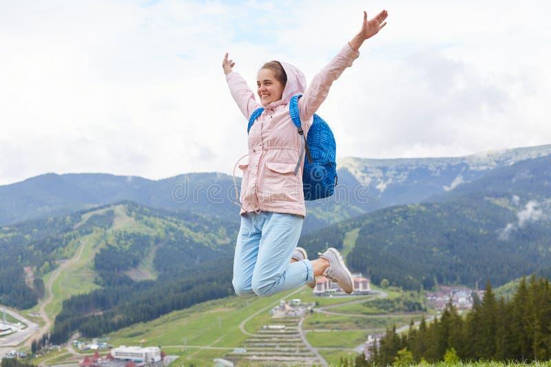 Plenerowy strzał kobiety doskakiwanie w górę wysokości, port wycieczkuje na wakacjach Żeńska jest ubranym różowa kurtka i błękitn fotografia royalty free