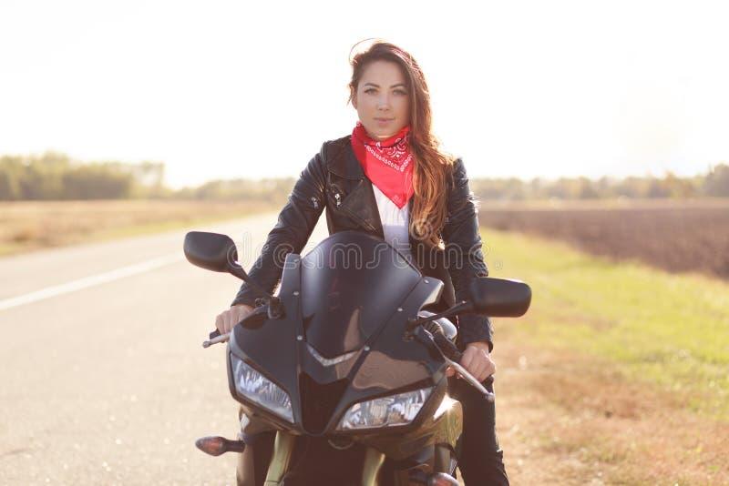 Plenerowy strzał piękny motocyklista długą podróż na jej motocyklu, jest ubranym czerwone eleganckie bandany i skórzana kurtka, l zdjęcie stock