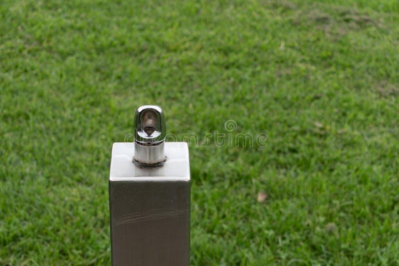 Plenerowy wody pitnej spout na zielonej trawie obrazy royalty free
