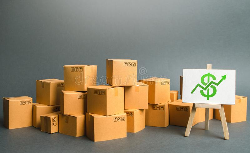 Plenty of cardboard boxes and sign with a dollar symbol green up arrow. rate growth of production of goods and products. Increasing economic indicators stock photo