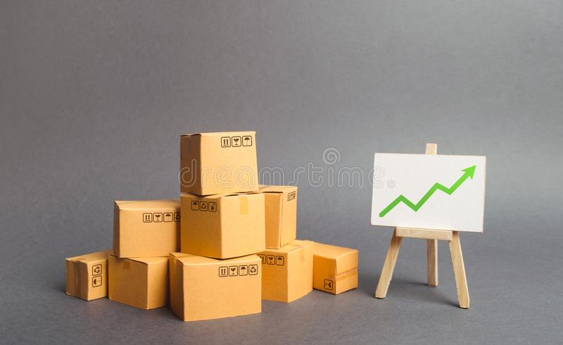Plenty of cardboard boxes and whiteboard with green positive chart arrow up. Increasing consumer demand. rate growth of production. Of goods and products royalty free stock photography