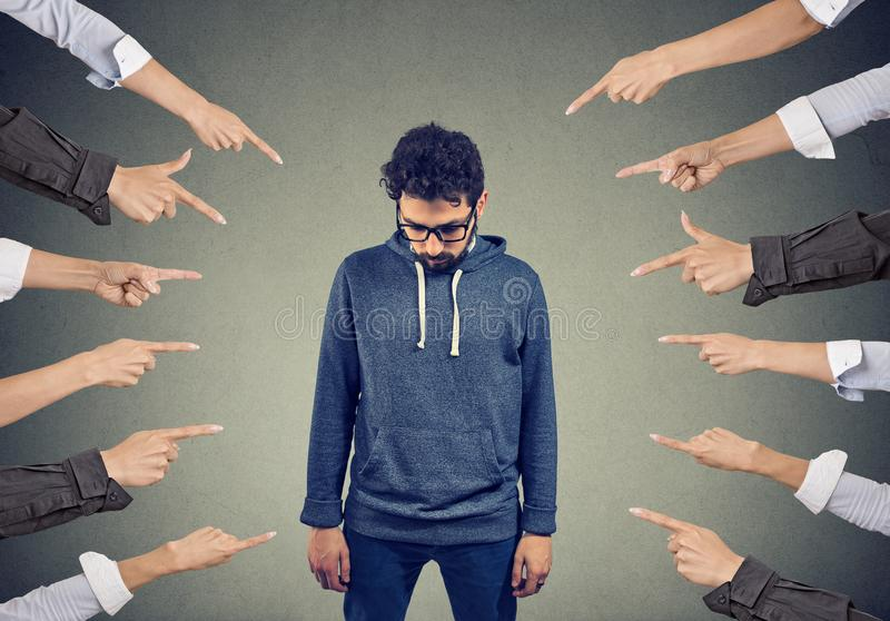 Bullied man. Public accusation concept. Plenty of crop hands fingers pointing at young man feeling guilty and being introvert stock photo
