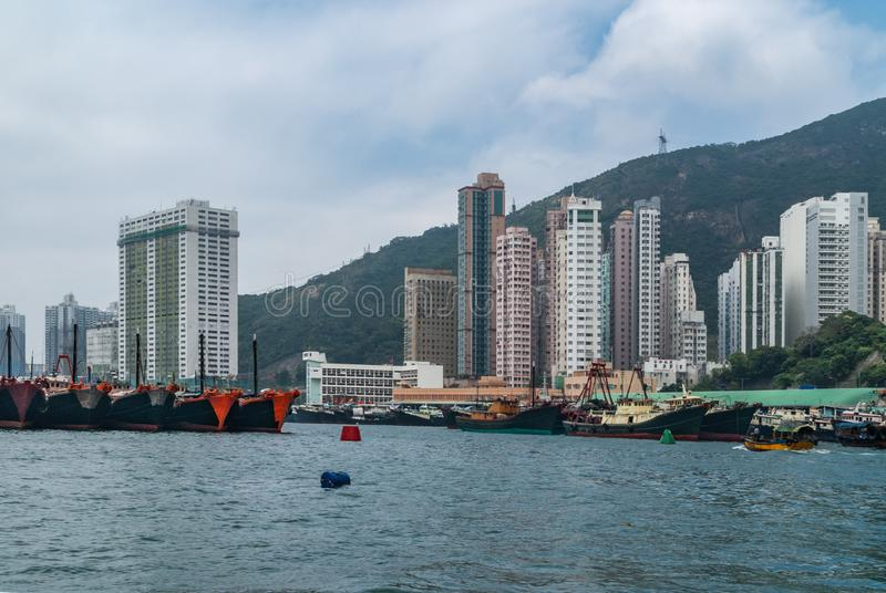 Plenty fishing vessels docked in front of tall buildings in harbor of Hong Kong, China. Hong Kong, China - May 12, 2010: Wide shot. Plenty black and red fishing royalty free stock images