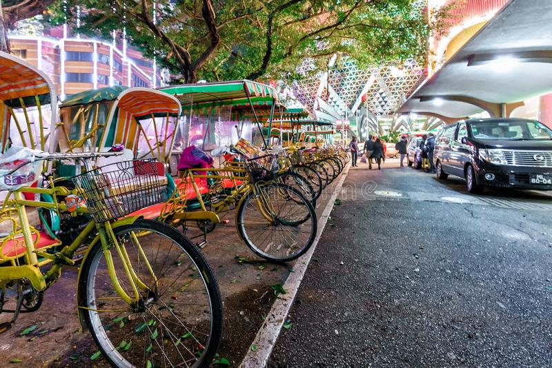 Plenty of yellow bicycles parked in a row at Grand Lisboa Hotel and Casino at night on city street illumination background stock images