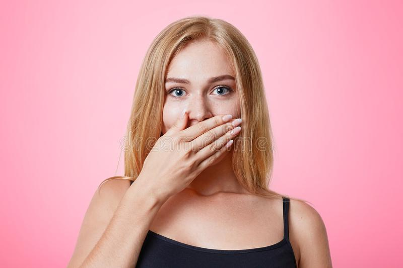 Plesant looking light haired female dressed casually, covers mouth with hand, tries to keep silent and not tell secret, isolated o royalty free stock photos