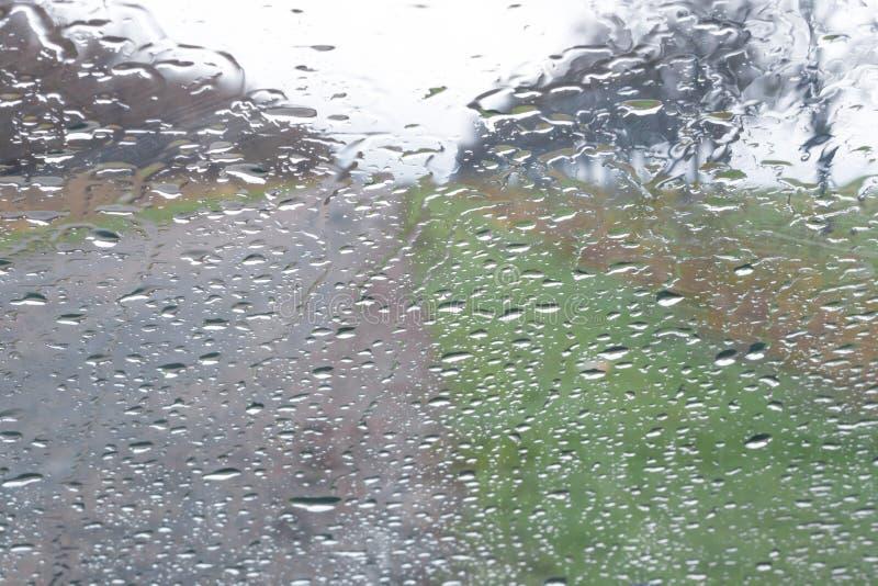 Pleuvoir la baisse sur la fenêtre avant de voiture, vue de route par la fenêtre photo libre de droits