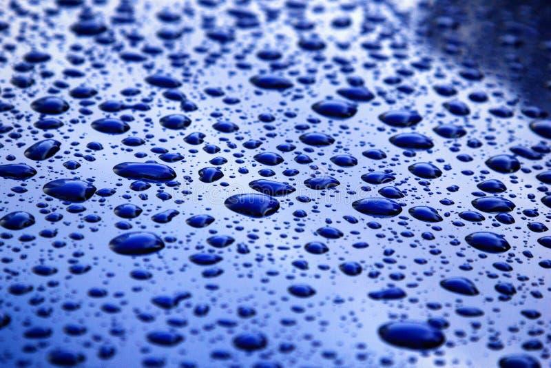 Pleuvoir les baisses sur la carrosserie bleue, foyer peu profond photographie stock libre de droits