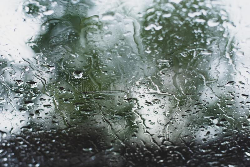 Pleuvoir les baisses sur la fenêtre avant de voiture dans le ton vert-foncé, seul et l'ab photographie stock