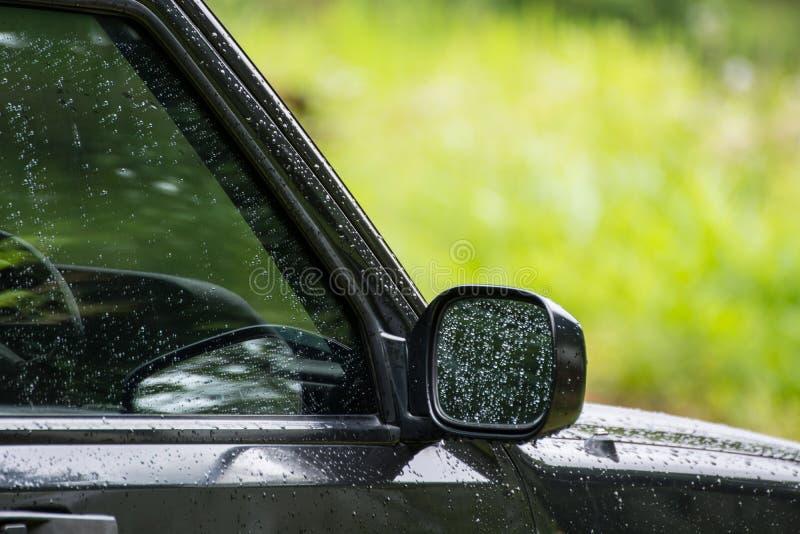 Pleuvoir les baisses sur la fenêtre et le verre latéral de miroir de la voiture, abstraits photo libre de droits