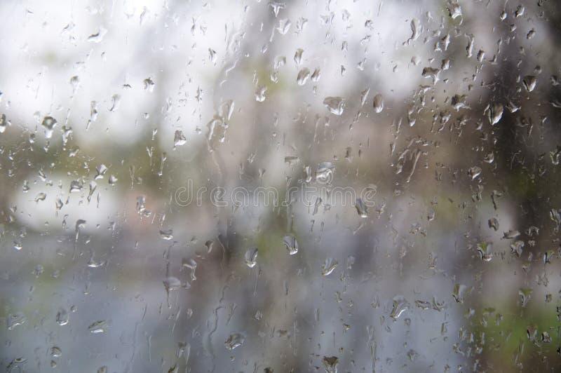 Pleuvoir les gouttelettes fonctionnant vers le bas sur une fenêtre, fond abstrait Concept d'automne d'automne Jour ennuyeux nuage image libre de droits