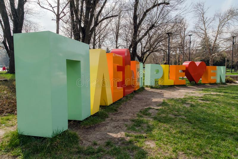 PLEVEN, BULGÁRIA - em março de 2019: O Pleven assina no parque em letras do alfabeto do cirílico e de latino fotos de stock