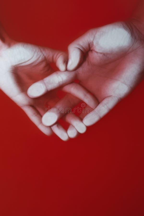 Plexus av händerna av en man och en kvinna i form av hjärta i rött vatten, begrepp av förälskelse och troheten, gåtakonst arkivbild