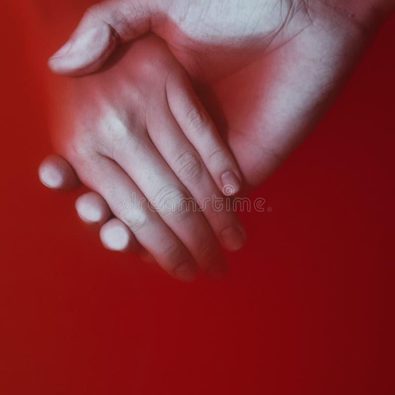 Plexus av händerna av en man och en kvinna i kulört rött blodigt vatten, begrepp av förälskelse och lojalitet royaltyfria foton