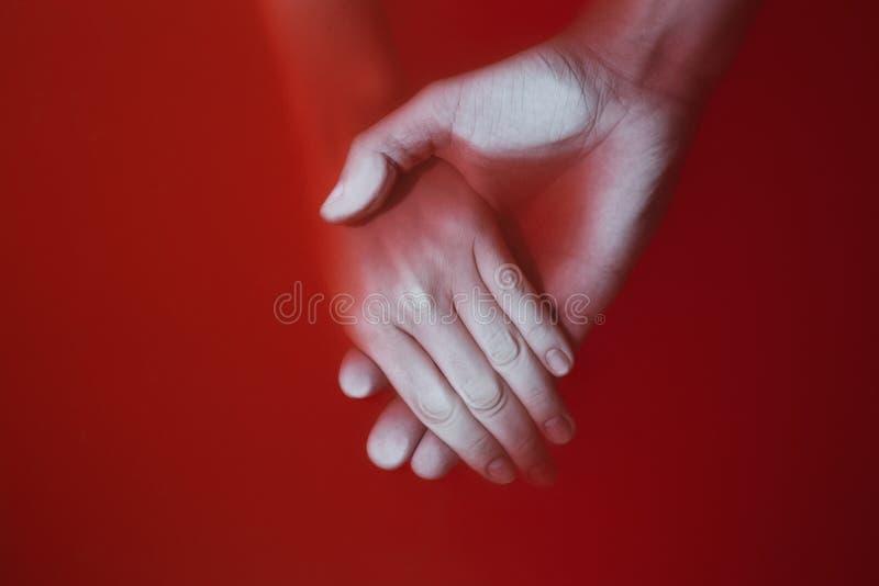 Plexus av händerna av en man och en kvinna i kulört rött blodigt vatten, begrepp av förälskelse och lojalitet fotografering för bildbyråer
