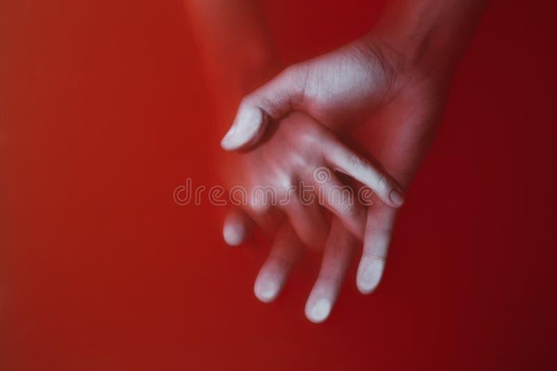 Plexus av händerna av en man och en kvinna som drunknar i liknande rött vatten för att ge första erfarenhet, täcka av en thriller arkivfoton