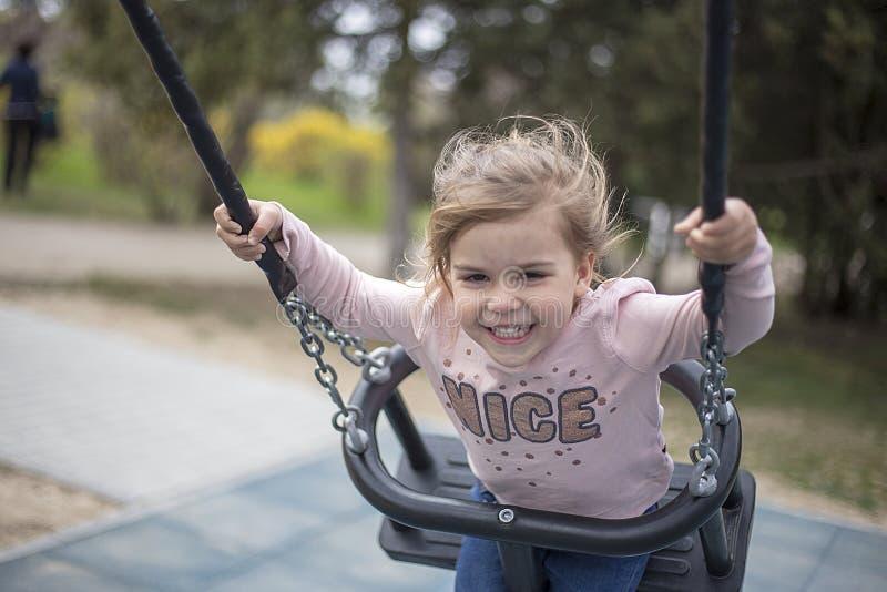 Plezier van een klein meisje van het berijden op een schommeling royalty-vrije stock fotografie