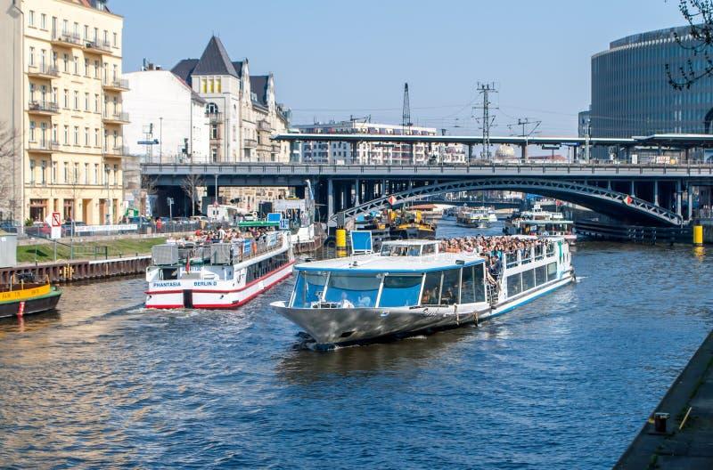 Plezierboten met mensen op de Fuifrivier in Berlijn met de spoorwegbrug en andere buildins op de achtergrond royalty-vrije stock fotografie