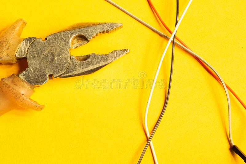 Pliers and colorful wires on yellow background. working tool stock images