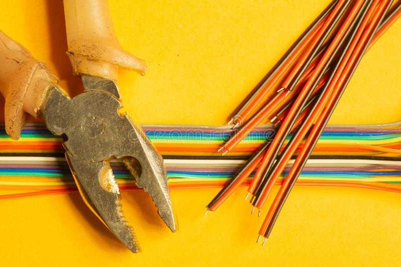 Pliers and colorful wires on yellow background. working tool royalty free stock photos