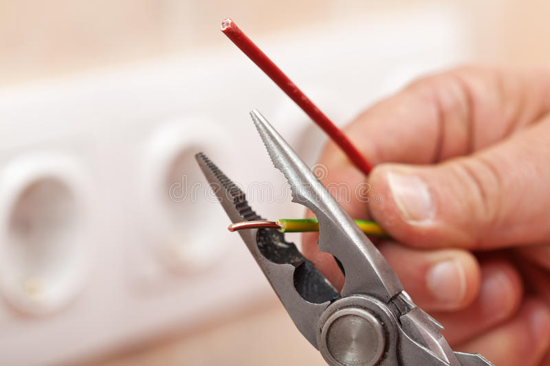 Pliers peeling copper wires - closeup stock image
