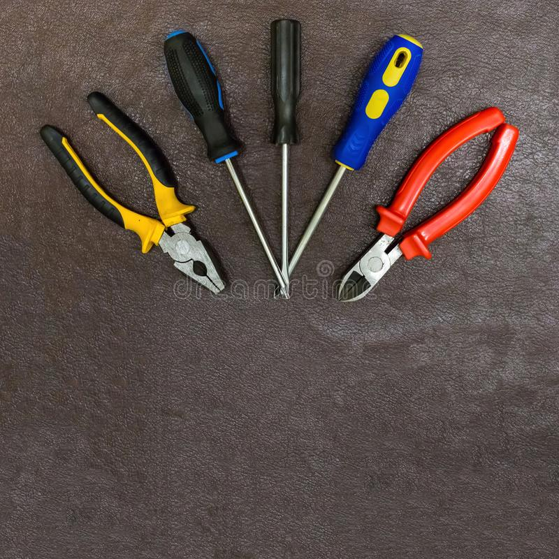 Pliers pliers with plastic bright pens protection set of screwdrivers on a dark brown background with copy spase base design royalty free stock images