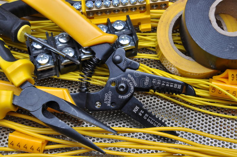 Pliers strippers with electrical component kit. On metal surface stock photo
