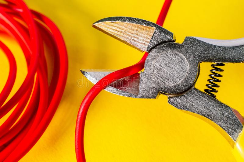 Pliers tool cutting red electric wire closeup on a yellow background royalty free stock photography