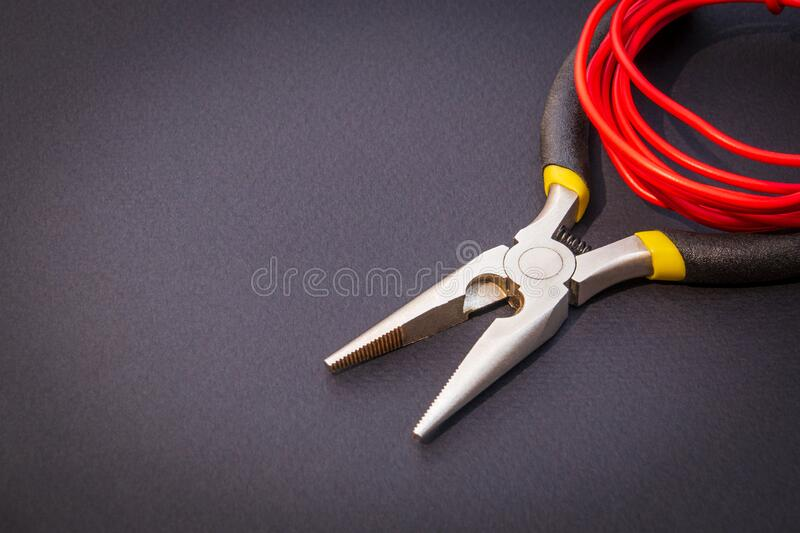 Pliers tool and red wires for electrician closeup, service and repairing concept stock photos