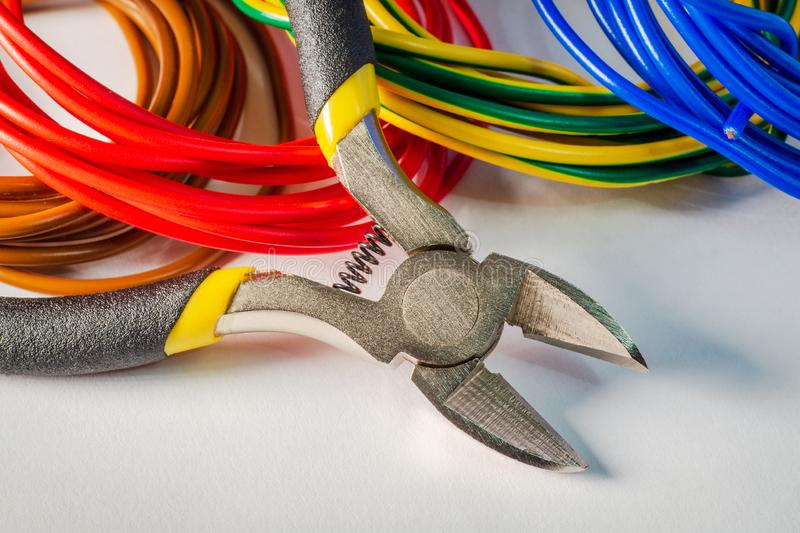 Pliers tool and wires for electrician closeup on gray background royalty free stock image
