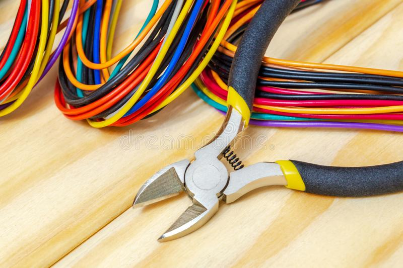 Pliers tool and wires for electrician closeup service repairing concept on wooden boards royalty free stock photography