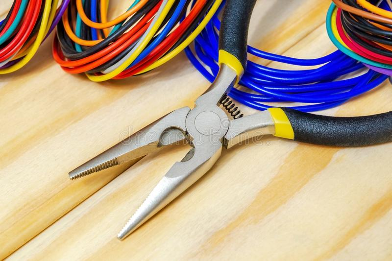 Pliers tool and wires for electrician closeup service repairing concept on wooden boards royalty free stock images