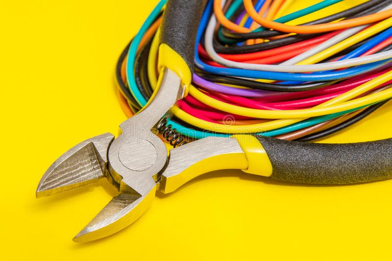 Pliers tool and wires for electrician closeup service repairing concept on yellow background royalty free stock photos
