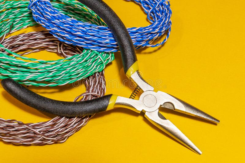 Pliers tool and wires for electrician closeup service repairing concept on yellow background royalty free stock images
