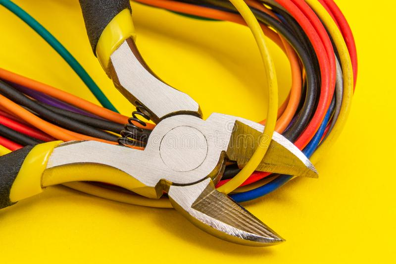 Pliers tool and wires for electrician closeup service repairing concept on yellow background royalty free stock photo
