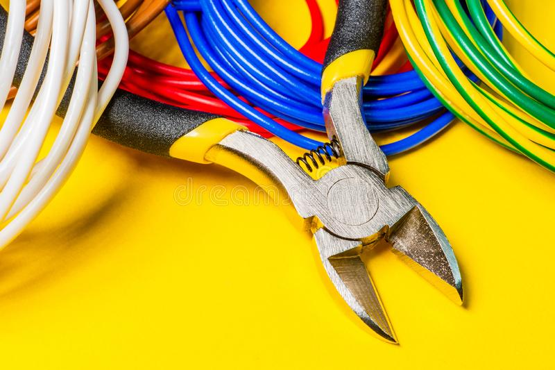 Pliers tool and wires for electrician closeup on yellow background stock images