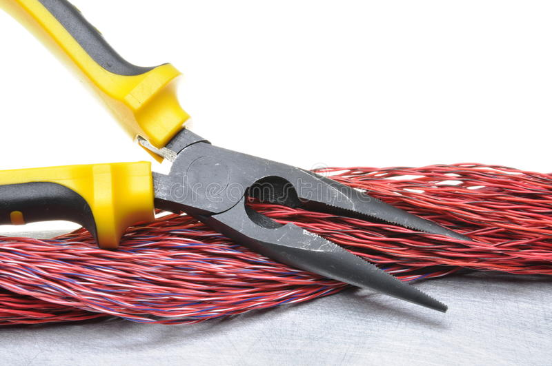 Pliers tools and cables on metal surface with white background stock photo