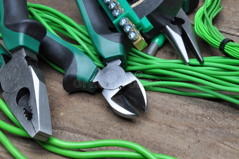 Pliers tools and component for electrical installation. On wooden board royalty free stock images