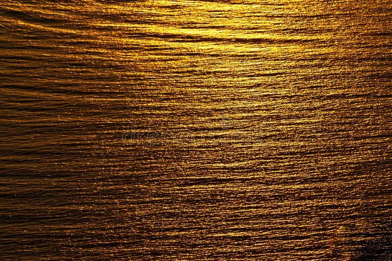 Plissado dourado da reflexão do por do sol do fundo do sumário na água foto de stock royalty free